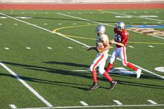 american football player chasing opposing receiver with ball during competiti - stock photo