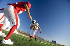 american football player running with ball at opposing team during competitiv - stock photo