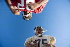 american football player running with ball at opposing player during competit - stock photo