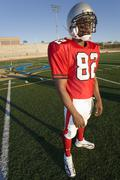American football player standing on pitch in red football strip and protecti Kuvituskuvat