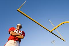 american football player, in red football strip and protective helmet, standi - stock photo