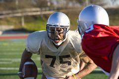 determined american football player running with ball at opposing players dur - stock photo