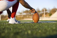 American football player attempting to kick field goal, teammate holding ball Stock Photos