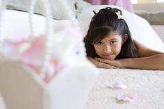 Girl (8-10), in bridesmaid's dress, lying face down on carpet in living roo Stock Photos