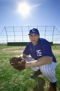baseball player, wearing number '25' blue uniform and glove, crouching on - stock photo