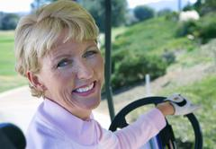 mature woman driving golf buggy on golf course, looking over shoulder, smilin - stock photo