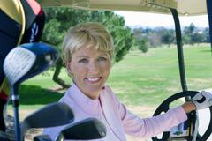 mature woman driving golf buggy on golf course, smiling, side view, portrait - stock photo