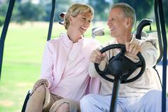 mature couple sitting in golf buggy on golf course, man driving, smiling, fro - stock photo
