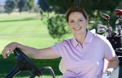 Mature woman, in pink polo shirt, sitting in golf buggy on golf course, smili Stock Photos