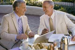 two mature businessmen sitting at outdoor restaurant table, one man using lap - stock photo