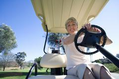 mature woman, in striped polo shirt, sitting in golf buggy on golf course, sm - stock photo