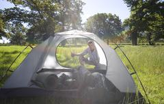 Young man crouching behind incomplete dome tent on camping trip in woodland c Stock Photos