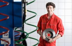 Male car mechanic, in red overalls, standing in commercial garage, holding ve Stock Photos