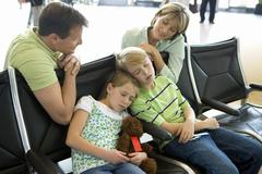 parents looking at children sleeping on seats in airport departure lounge, gi - stock photo