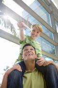 Father carrying son (8-10) on shoulders in airport, boy holding toy aeroplane Stock Photos