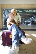 Woman standing beside luggage trolley in airport, daughter (7-9) sitting on s Stock Photos
