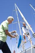Stock Photo of two mature men preparing to set sail on yacht, one man untying mooring rope,