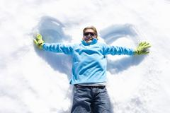 boy (7-9) lying in snow making 'angel wings', smiling, overhead view - stock photo