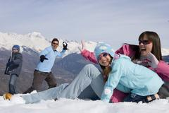 Family of four having snow ball fight in snow field, smiling, mountain range  Stock Photos