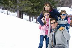 Family of four embracing in snow field, wearing sunglasses, smiling, portrait Stock Photos
