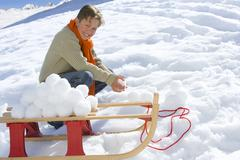 boy (7-9) crouching in snow by sled and snowballs, smiling, portrait - stock photo