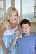 Mother and son (6-8) holding toothbrushes in bathroom, smiling, portrait Stock Photos