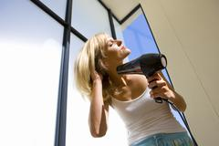 young woman blow drying hair outdoors, low angle view - stock photo