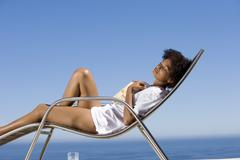 young woman lying on deck chair with book by sea, eyes closed, side view - stock photo