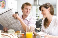 Couple having breakfast at kitchen table, man holding newspaper and smiling a Stock Photos