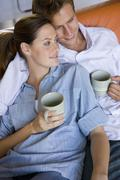 Couple sitting together on sofa, holding mugs, elevated view Stock Photos