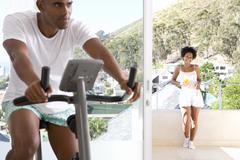 Man on stationary bicycle indoors, woman smiling on balcony in background Stock Photos