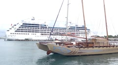 Big cruise ship and wooden sailboat in the harbour of Papeete Stock Footage