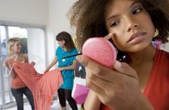 three teenage girls (15-17) in bedroom, girl applying make-up in foreground - stock photo
