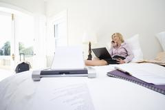 mature businesswoman using laptop and mobile phone on bed, smiling, printer o - stock photo