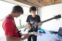 Two teenage boys (16-18) playing guitars in garage Stock Photos