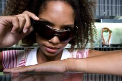 young woman lowering sunglasses on nose, portrait, close-up - stock photo