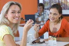 Two young woman eating in cafe, smiling, young man smiling in background Kuvituskuvat