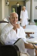 mature man wearing white bath robe, sitting in deck chair with glass of water - stock photo