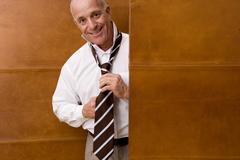 Mature man adjusting tie, smiling, portrait Stock Photos