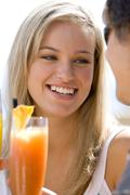 Young woman by cocktail, smiling at friend, close-up Stock Photos