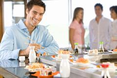young man sitting at sushi bar, smiling, portrait - stock photo
