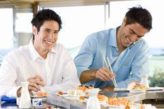 two men eating in sushi bar, smiling, portrait - stock photo