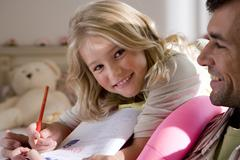 Girl (6-8) doing homework by father, smiling, portrait Stock Photos