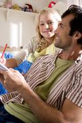 Father helping daughter (6-8) with homework, smiling, portrait of girl Stock Photos