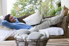 Stock Photo of man lying on sofa with laptop on lap, smiling, portrait, bowl of pebbles in f