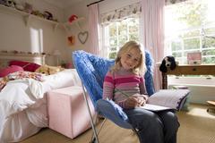 Girl (8-10) in bedroom doing homework on blue shag pile chair, smiling, portr Stock Photos