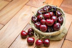 fresh red cherries on wooden table - stock photo