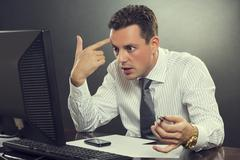 desperate businessman pointing his finger to his head - stock photo