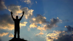 A Man Worships God Silhouetted Against a Sunset 4K Stock Footage