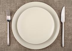 Table setting. Beige plate, fork, knife and beige linen tablecloth Stock Photos